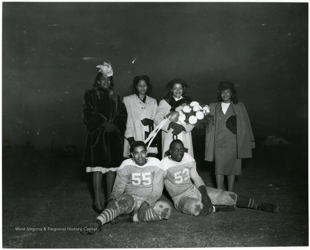 Four female students standing in the back row.  Two football players seated on the ground.