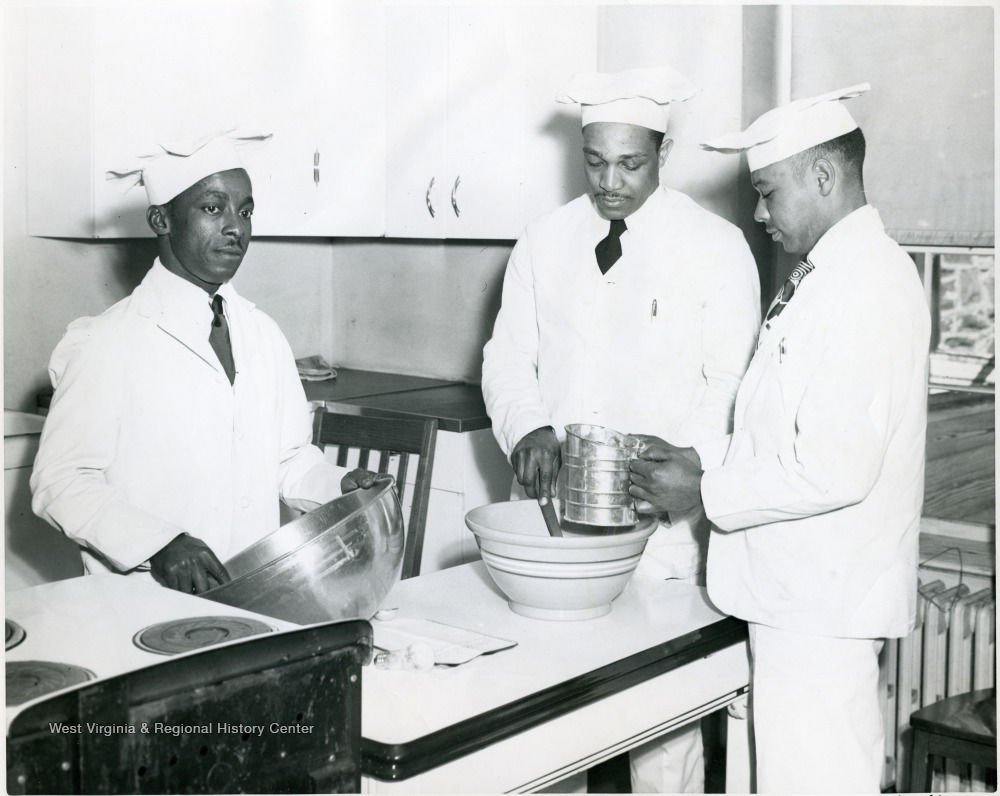 Three students sifting flour over a bowl.