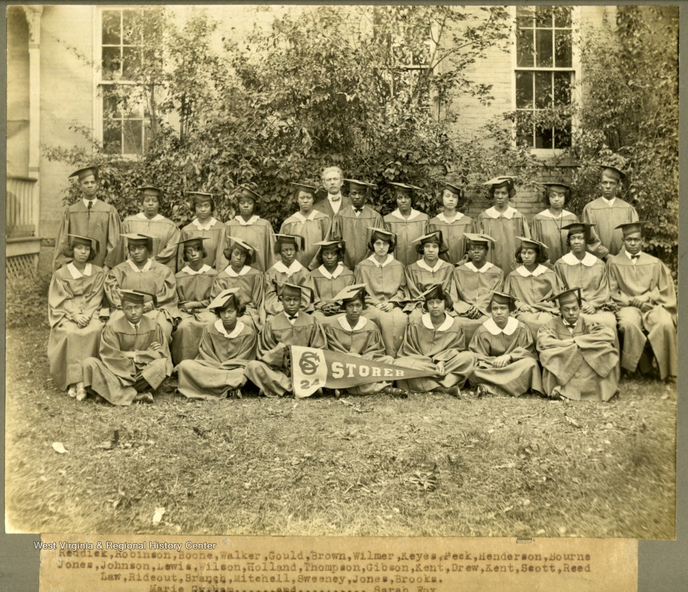 Class of 1924 in caps and gowns at Storer College with college Pres. McDonald. First Row: Reddick, Robinson, Boone, Walker, Gould, Brown, Wilmer, Keyes, Peek, Henderson, Bourne. Second Row: Jones, Johnson, Lewis, Wilson, Holland, Thomson, Gibson, Kent, Drew, Kent, Scott, Reed. Third Row: Law, Rideout, Branch, Mitcehell, Sweeney, Jones, Brooks. Absent from photo: Marie Graham and Sarah Fox.