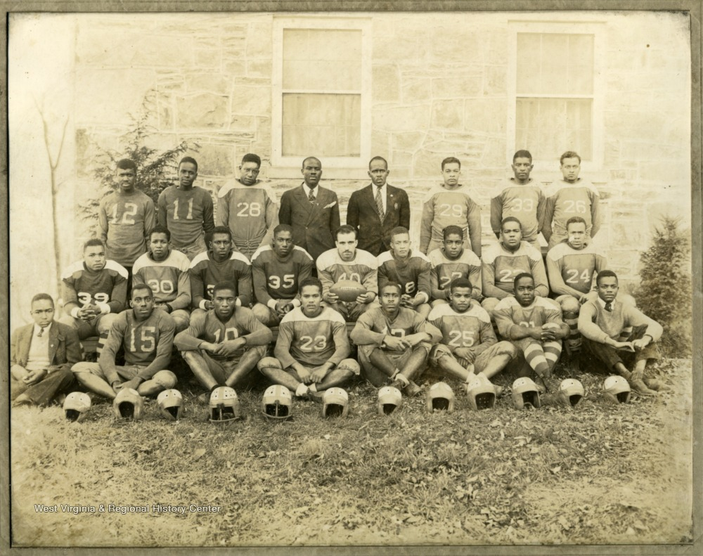 Storer College football team in uniform by building.