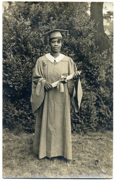Graduation portrait of African-American student Bernell Bows in cap and gown holding her diploma.  Bows graduated from Storer in 1933.