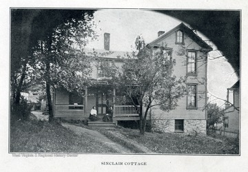 Two African-American ladies seated on the porch of Sinclair Cottage.