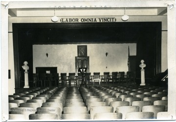 Sign over the stage reads 'Labor Omnia Vincit.'