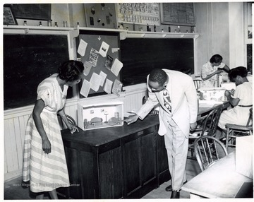 African-American instructor, T. W. Stanback, examines a set made by a student, Mrs. Callahan.