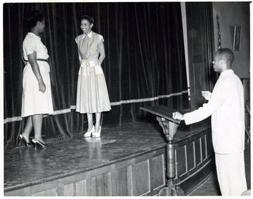 African-American students on a stage with an African-American teacher directing them.