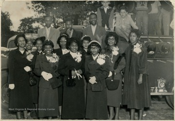 Group portrait of African-American male and female students, possibly the Homecoming Court, at Storer College's homecoming football game in 1952.