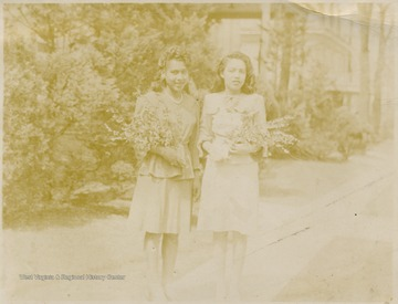 Two female African-American students hold flowers.