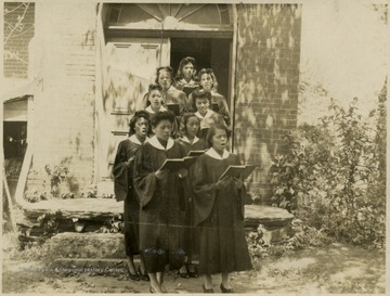 Group of African-American, female students, dressed in choir robes exit a church singing.