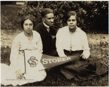 L to R:  Isabelle Stewart, Raymond McNeal and Odetta Johnson display a Storer pennant sitting on the campus lawn. All three students are listed as Honor Students in 1916.