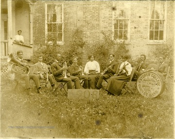 Group portrait of Storer College Cornet Band members with instruments on lawn. Pictured: 'B. Debbis, C. Dennis, John W. McKinney, T. Herrod, Trulia Jones, Eugene Jones, C. McKinney, Prof. Saunders, W. Harris.'