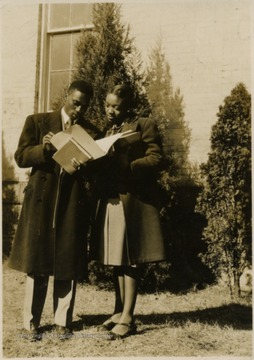 A male and female student stand outside looking at papers in a file together.