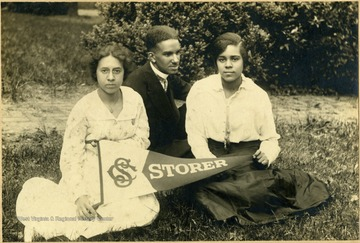 Isabelle Stewart, Raymond McNeal, and Odetta Johnson sit on the lawn at school holding a school pennant.