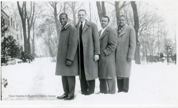 Four male Storer students pose for a portrait on a snowy day.