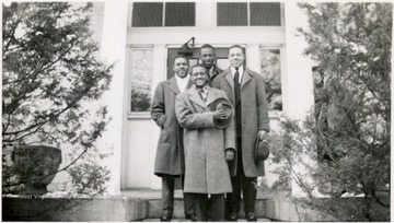 Four male Storer students pose for a portrait on the steps of a building.