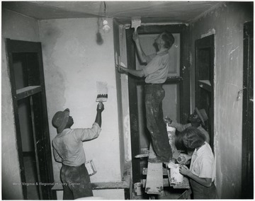 Students paint the inside of a room.