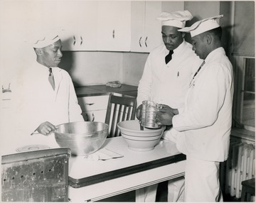 Three students stand around a table sifting flour over a bowl.