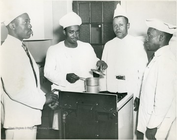 Four male students with a pot on a stove.