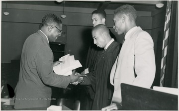 Student in a gown shakes a man's hand.