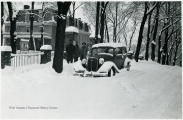 Storer students stand next to snow covered car during the great snow of March 7, 8, 9, 1941.
