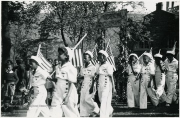 Eight Black girls carry flags in a parade.