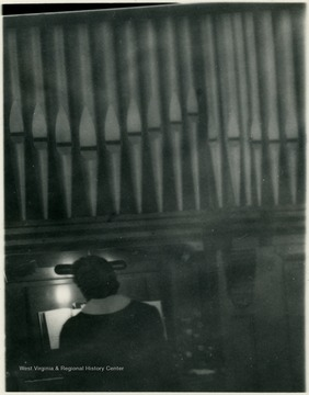 Organist playing a pipe organ.