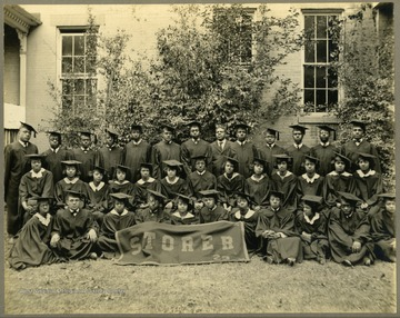 Group shot of Storer College class of 1923 in front of building and tree.