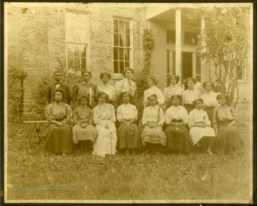 Mrs. McKinney's Class in front of building. All women except one male, first left on back row.