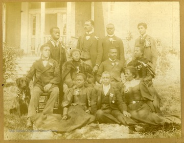 Group shot of Storer College students sitting and standing on lawn with dog.