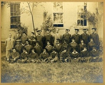 Group shot of graduating class in caps and gowns in front of building on Storer College Campus. Pres. McDonald in middle.