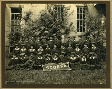 "Group photo of Storer College class of 1932 in caps and gowns in front of building with ""STORER"" banner. College President McDonald in back row."