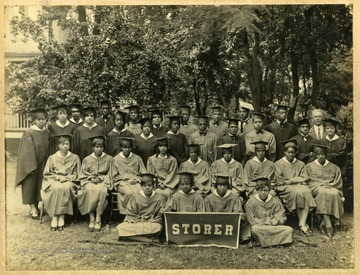 Storer College class of 1929 in caps and gowns on law of campus. First Row: Finely-(?, Moore,-Edwards. Second Row: Coleman, Heath, Stevens, Johnson, Holland, Morris, Dixon, Bibby. Standing: Spencer, Harris, Brown, Daily, Johnson, Tall, Heath, Brooks, Brown, Wilson, Hill, Perry, Sims, Johnson, Pierce, Carroll, Thomas, Washington, Pres. McDonald. Jackson.