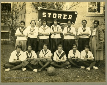 Team portrait of Storer College girl's basketball team in uniform in front of STORER banner.