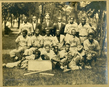Group photo of Storer College baseball team in uniform on lawn of campus. First Row: Tomlinson(P), Taylor, Pres. McDonald, McGhee, Scorey, Craig (R.F.), Scott (1st & 2ndB, captain). Second Row: Fisher (LF) Howard (CF) King (P), Tindley (C), Green (C), Wheaton (2ndB). Third Row: Crawford (P), Yarbrough, Mossett (SS), Morris