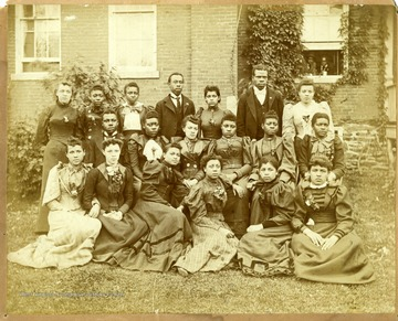 Group photo of Storer College students in front of building. Two people looking out window on right.