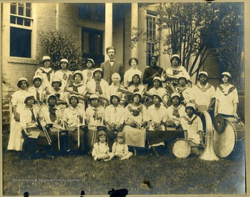 Storer College band members in uniform with instruments in front of building. Pres. & Mrs. McDonald in back row.