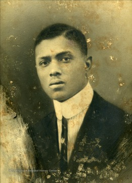 "A young African American man, possibly a student, in a suit  wearing ""ARROW""-style collar and thin tie."