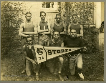 Storer College Track team in uniform by building.