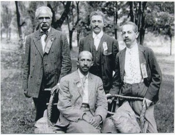 Seated is W.E.B. Du Bois. Standing, from left to right, is J. R. Clifford, L. M. Hershaw, and F. H. M. Murray.